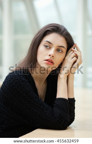 Portrait of melancholy young beautiful brunette woman in a black sweater on a light geometric blurry background