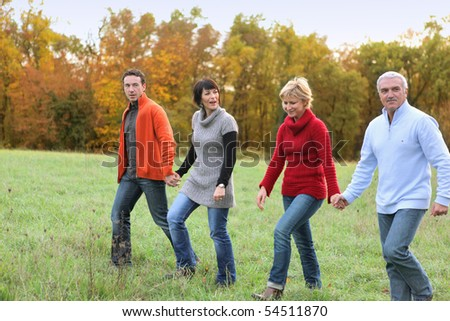 Portrait of men and women having a walk in the countryside - stock photo