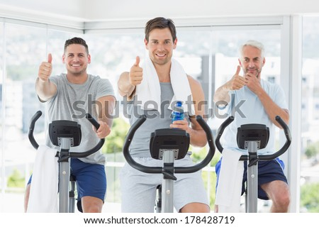 Portrait of men on exercise bikes gesturing thumbs up at gym - stock photo