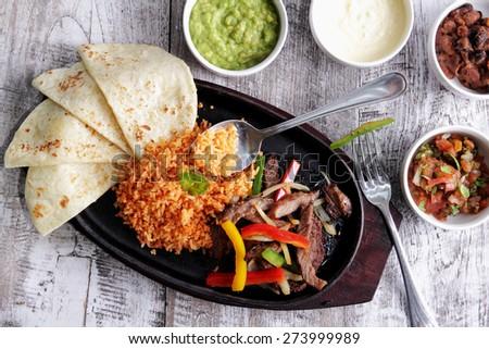 portrait of mexican cuisine fajitas served with soft flour tortillas, rice, bean chili, salsa, guacamole and sour cream - stock photo