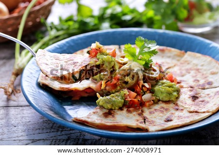 portrait of mexican cuisine quesadilla served at blue plate with guacamole, salsa and jalapenos - stock photo