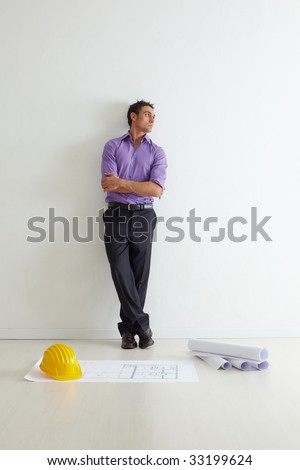 portrait of mid adult architect leaning on wall and looking away. Copy space - stock photo