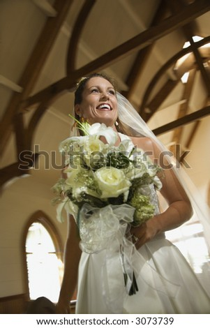 Portrait of mid-adult bride holding bouquet leaving a church. - stock photo