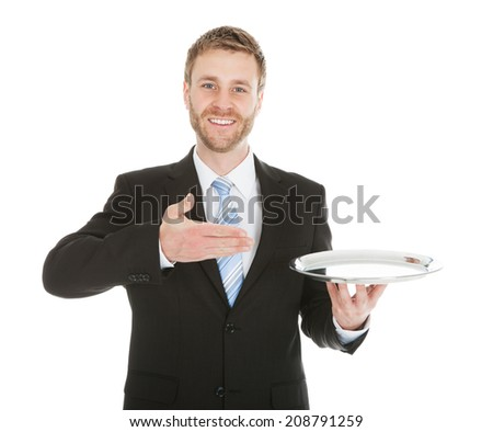 Portrait of mid adult businessman holding empty tray over white background - stock photo