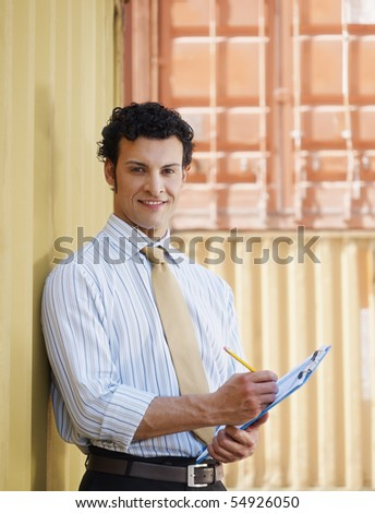 portrait of mid adult businessman leaning on cargo container and looking at camera. Vertical shape, front view, copy space - stock photo