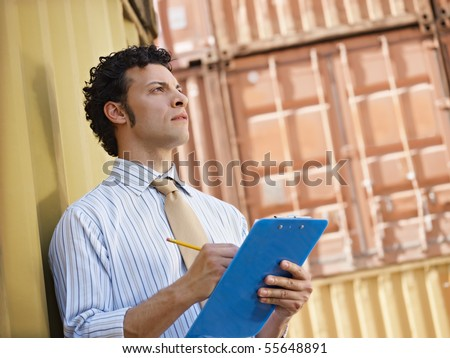 portrait of mid adult businessman leaning on cargo container and looking up. Horizontal shape, side view, copy space - stock photo