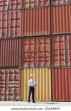 portrait of mid adult businessman standing near cargo containers and holding clipboard. Vertical shape, full length - stock photo