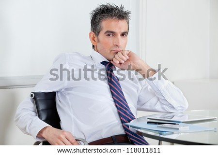 Portrait of mid adult businessman with digital tablet relaxing at desk in office - stock photo