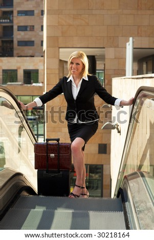 portrait of mid adult businesswoman on escalator, looking at camera - stock photo