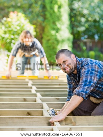 Portrait of mid adult carpenter holding drill at construction site - stock photo