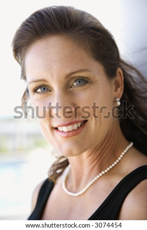 Portrait of mid-adult Caucasian female smiling and making eye contact. - stock photo