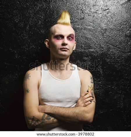 Portrait of mid-adult Caucasian male punk with his arms crossed. - stock photo