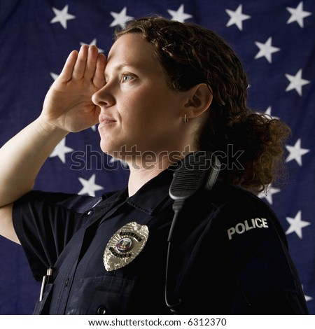 Portrait of mid adult Caucasian policewoman saluting with American flag as backdrop.