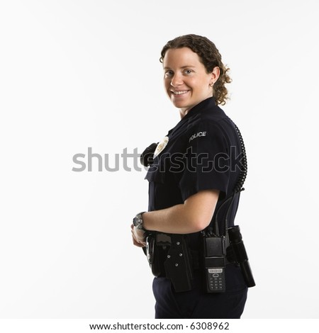 Portrait of mid adult Caucasian policewoman standing with hand on gun holster looking over shoulder at viewer smiling.