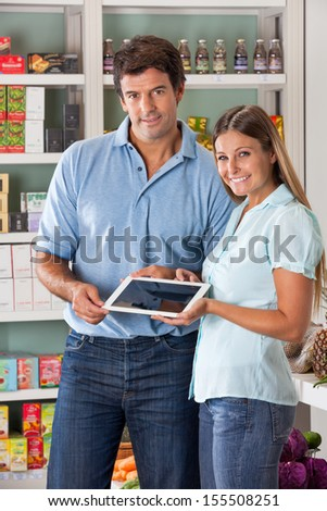 Portrait of mid adult couple holding digital tablet in supermarket - stock photo