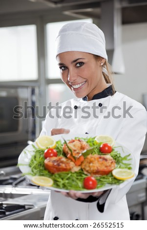 portrait of mid adult female chef in kitchen presenting dish - stock photo