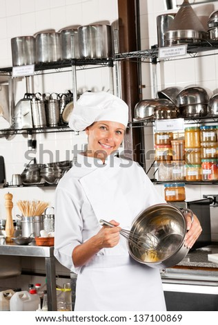 Portrait of mid adult female chef mixing egg with wire whisk in bowl at commercial kitchen - stock photo