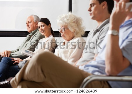 Portrait of mid adult female smiling while sitting amidst other people in hospital lobby - stock photo
