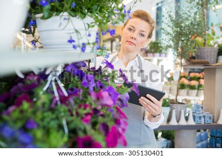 Portrait of mid adult florist holding digital tablet while standing by flower trolley in shop - stock photo