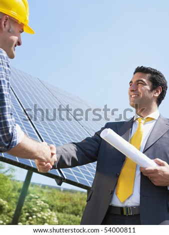 Portrait of mid adult italian male engineer holding blueprints and shaking hands to manual worker in solar power station. Vertical shape, low angle view. Copy space