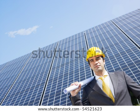 Portrait of mid adult italian male engineer holding blueprints in solar power station and looking up. Horizontal shape, front view. Copy space - stock photo