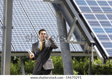 Portrait of mid adult italian male engineer holding blueprints in solar power station and talking on mobile phone. Horizontal shape, front view. Copy space - stock photo