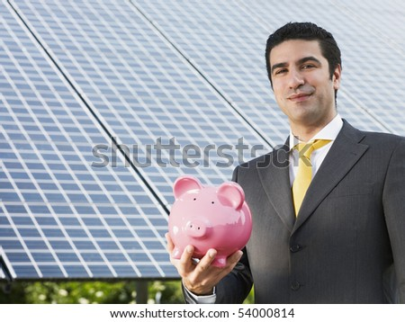 Portrait of mid adult italian male engineer holding piggy bank in solar power station, smiling at camera.Horizontal shape, front view. Copy space - stock photo