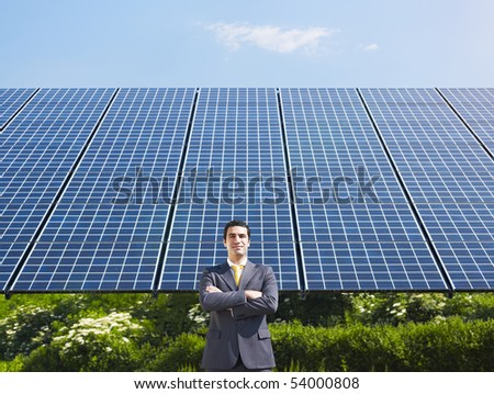 Portrait of mid adult italian male engineer with arms folded in solar power station, smiling at camera.Horizontal shape, front view. Copy space - stock photo