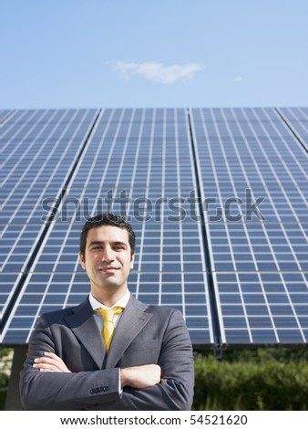 Portrait of mid adult italian male engineer with arms folded in solar power station, smiling at camera. Vertical shape, front view. Copy space - stock photo