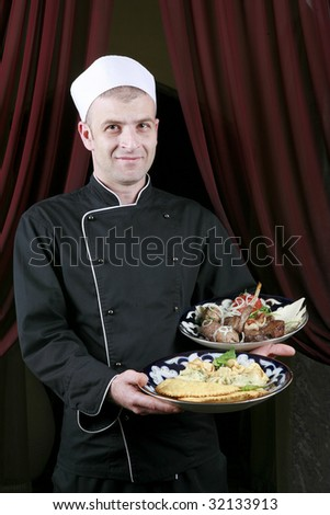 portrait of mid adult male chef in kitchen presenting dish - stock photo