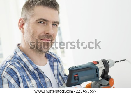 Portrait of mid-adult man drilling hole in wall - stock photo