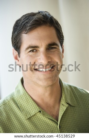 Portrait of mid adult man smiling towards the camera. Vertical shot. - stock photo