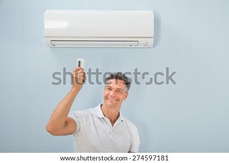 Portrait Of Mid-adult Man Using Air Conditioner - stock photo