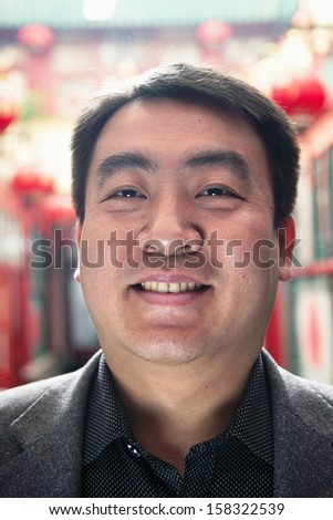 Portrait of mid adult man with Chinese lanterns in background - stock photo