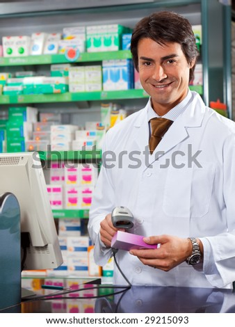 portrait of mid adult pharmacist scanning medicine with barcode reader - stock photo