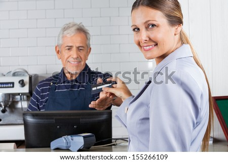 Portrait of mid adult woman giving credit card to male cashier at cash counter - stock photo