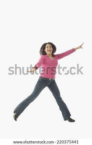 Portrait of mid adult woman jumping in air - stock photo