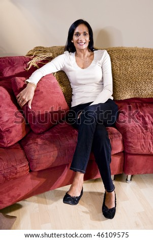 Portrait of mid-adult woman of Indian ethnicity relaxing at home in living room  on sofa - stock photo