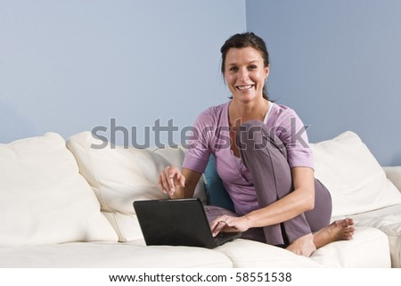 Portrait of mid-adult woman sitting on couch at home with laptop - stock photo