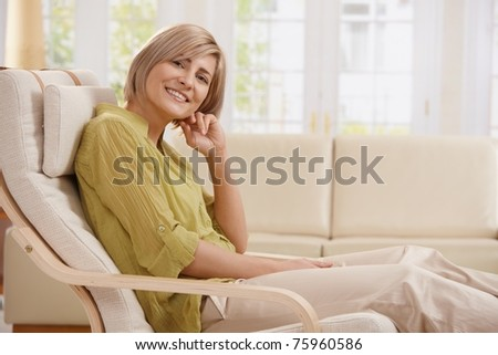 Portrait of mid-adult woman smiling at camera sitting in armchair in bright living room with hand up at face.? - stock photo