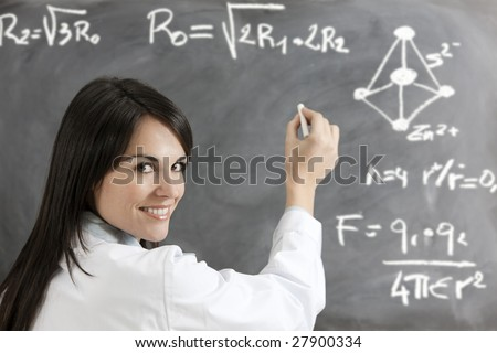 portrait of mid adult woman writing chemical formula on blackboard - stock photo