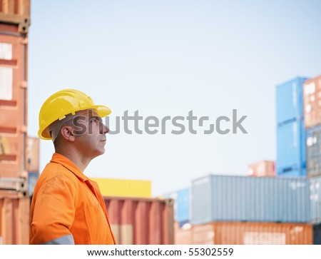 portrait of mid adult worker looking at cargo containers. Horizontal shape, side view, copy space - stock photo
