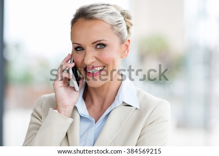 portrait of mid age businesswoman talking on cell phone  - stock photo