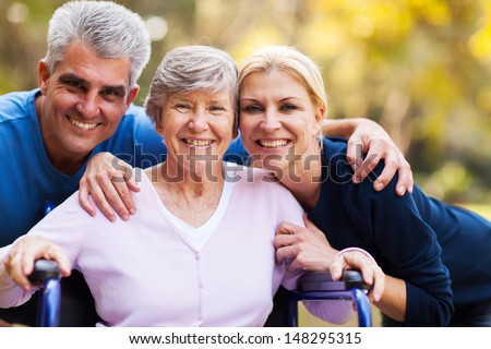 portrait of mid age couple and senior mother outdoors - stock photo