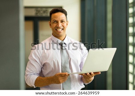portrait of mid age employee holding laptop