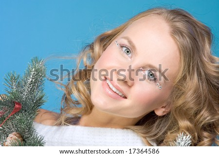 Portrait of mid-aged beautiful blonde female surrounded by branches of decorated Christmas tree