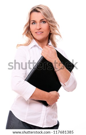 Portrait of mid aged woman in office suit smiling with laptop in hands