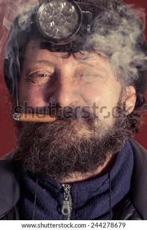 Portrait of midage man with beard smoking cigar.  - stock photo