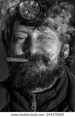 Portrait of midage man with beard smoking cigar - stock photo