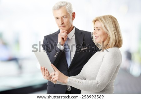 Portrait of middle age business woman and senior businessman working at digital tablet while standing at office.  - stock photo